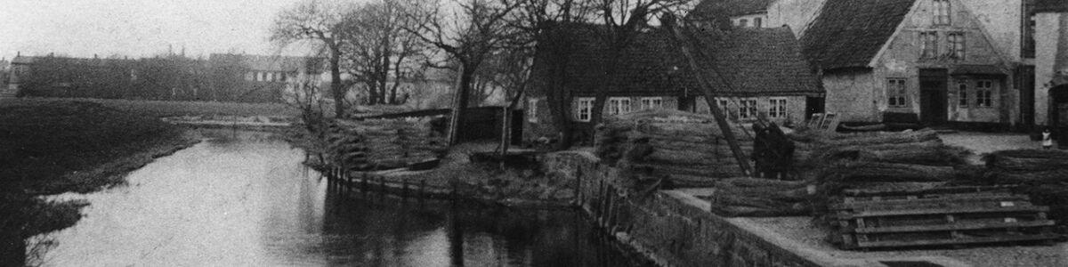 Skibbroen i Tønder med kran og stabler af tagrør. I baggrunden Kogade. Ca.1900